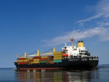 Ship with yellow, red, blue, green cargo. Ship with yellow red blue green cargo reflected in a blue see at the blue background Royalty Free Stock Photos