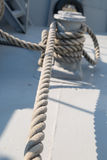 Shipboard Rope. Close up detailed top view of grey nautical rope at an open deck of a ship Stock Photos