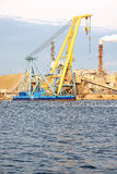Shipbuilding crane. Industrial scene of a shipbuilding crane floating by a dock with a smoking chimney in the background Stock Photography