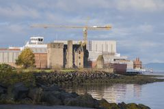 Shipbuilding With Crane and Newark Castle In Port Glasgow Scotland Coast sea Beach Traditional Industry. Shipbuilding using large crane next to Newark castle on Stock Image