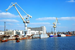 Shipbuilding cranes. And some sea ships near a pier Royalty Free Stock Photos