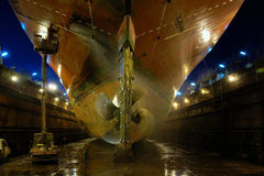 Shipbuilding in a dry dock. Looking up at the hull of a large ocean going vessel that was built in a dry dock and is being prepared to be painted royalty free stock photo