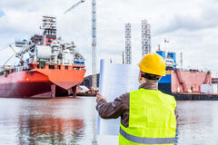 Shipbuilding engineer checking documents at the dock side in a port. Shipbuilding engineer checking documents and plans of construction at the dockside in a stock photo