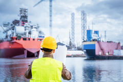 Shipbuilding engineer checking documents at the dockside in a port. Shipbuilding engineer checking documents and plans of construction at the dockside in a port Stock Photos