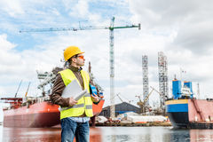 Shipbuilding engineer at the dock side in a port. Shipbuilding engineer stands at the dockside in a port. Wearing safety helmet, yellow vest and safety glasses royalty free stock photos