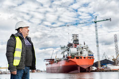 Shipbuilding engineer at the dockside in a port. Shipbuilding engineer stands at the dockside in a port. Wearing safety helmet and yellow vest. Shipbuilding stock photos