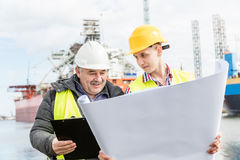 Shipbuilding engineer explains technical matters with a student worker. Shipbuilding engineer discusses documents with a student. Experienced worker wearing Royalty Free Stock Photos