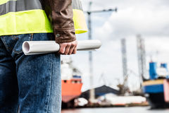 Shipbuilding engineer holding construction documents. Shipbuilding engineer stands at the dockside in a port. Man is holding construction documents Royalty Free Stock Photos