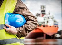 Shipbuilding engineer with safety helmet in shipyard. Shipbuilding engineer stands at the dockside in a port. Man is holding a safety helmet, close-up Stock Photo