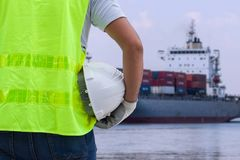 Shipbuilding engineer stands at the dockside in a port. Man is h. Olding a safety helmet Royalty Free Stock Images