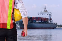 Shipbuilding engineer stands at the dockside in a port. Man is h. Olding a safety helmet Royalty Free Stock Photos