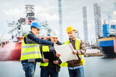 Shipbuilding engineers introducing new solution in a shipyard. All men wearing safety helmets and yellow vests. Transport industry stock photos