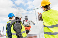 Shipbuilding engineers introducing new solution. Shipbuilding engineers introducing new solution in a shipyard. All men wearing safety helmets and yellow vests Royalty Free Stock Photography