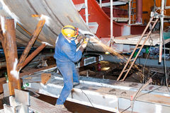 Shipbuilding fitter. Fitter grinding welds on the construction of external ballast tanks of an oil rig Stock Images