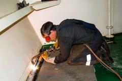 Shipbuilding fitter. Shipbuilding evaporates burner fitter on the ship deck Stock Photo