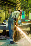 Shipbuilding fitter. Grinding in the production hall Stock Photos
