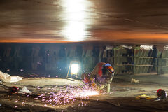 Shipbuilding fitter. Grinding weld on a new hull shipbuilding dock Stock Images