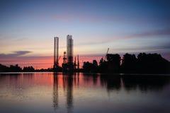 Shipbuilding sunrise. Drilling rig in repair in shipyard Gdansk, Poland Stock Photos