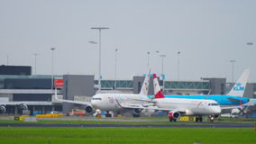 Shiphol airport traffic. AMSTERDAM, THE NETHERLANDS - JULY 26, 2017: Austrian Embraer 195 OE-LWL taxiing to the start and TUI Fly Boeing 767 HB-JJF taxiing after stock video footage