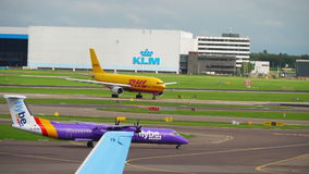 Shiphol airport traffic. AMSTERDAM, THE NETHERLANDS - JULY 29, 2017: DHL Airbus 300 D-AEAA on the start and FlyBe Bombardier Dash 8 Q400 G-JEDM taxiing. Shiphol stock video