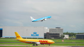 Shiphol airport traffic. AMSTERDAM, THE NETHERLANDS - JULY 29, 2017: DHL Airbus 300 D-AEAA on the start, FlyBe Bombardier Dash 8 Q400 G-JEDM taxiing and KLM stock footage