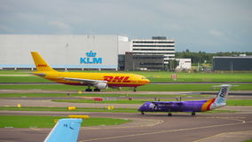 Shiphol airport traffic. AMSTERDAM, THE NETHERLANDS - JULY 29, 2017: DHL Airbus 300 D-AEAA on the start and FlyBe Bombardier Dash 8 Q400 G-JEDM taxiing. Shiphol stock footage