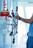 Shipmaster working on hand control on helm Stock Photo