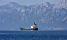 Shipping anytime, anywhere. Anchoring cargo ship in the bay of Antalya, Turkey, Toros mountain in the background royalty free stock images