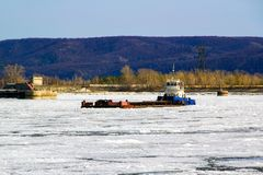 A shipping barge stands in the middle of an icy river royalty free stock photo