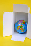 Shipping box. An open shipping box with Colourful globe.. ready to tape up and send royalty free stock images