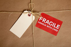 A Shipping box with a blank tag and a Fragile. A brown shipping box with a blank tag and a fragile sticker with copy space Royalty Free Stock Photos