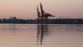Shipping and Cargo Cranes in Port of Vancouver with City Buildings Mount Baker and Water Reflection along English Bay at Sunrise stock footage