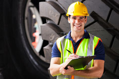 Shipping company employee. Portrait of shipping company employee standing in front of industrial tires Stock Photo
