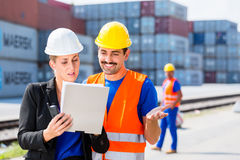 Shipping company workers in front of containers. Manager with clipboard full of freight documents talking with worker on shipment yard in front of container Royalty Free Stock Photos