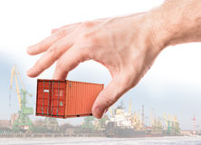 Shipping container in hand above port. Bright red metal freight shipping container in man's hand above port background stock photos