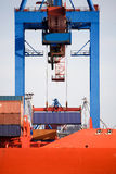 Shipping container loading. Shipping cargo container being loaded onto freighter in port Stock Photos