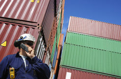 Shipping containers and dock worker. Dock and port worker talking in phone with stacks of freight containers in background Royalty Free Stock Photos