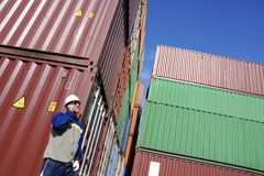 Shipping containers and dock worker. Dock and port worker talking in phone with stacks of freight containers in background Stock Photography