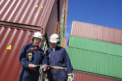 Shipping containers and dock workers. Dock and port workers talking, with stacks of freight containers in background inside commercial container port Royalty Free Stock Photography
