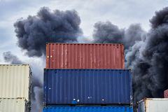 Shipping containers stacked in storage with plumes of black toxic smoke from a fire against a blue sky. royalty free stock photo