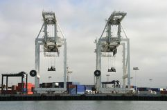 Shipping Cranes. Two large cargo cranes are poised to unload another container ship royalty free stock photo