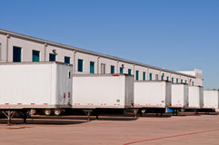 Shipping and Distribution Warehouse. A distribution warehouse with truck trailers lined up for loading and unloading shipments and cargo royalty free stock photos
