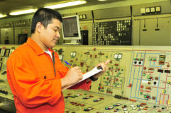 A shipping engineer. Near a panel of ship's automation Stock Photos