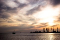 Shipping Port in the morning with sunrise. Seaport in the sunset rays of the sun. ship on the horizon at sunset royalty free stock photos