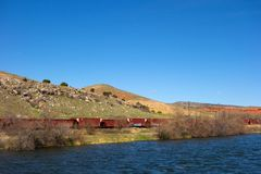 A cargo train traveling beside a river in wyoming. Shipping by rail as seen on a cloudless day in the springtime Royalty Free Stock Image