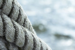 Shipping with ropes in front of water. Close up with clean ropes in foreground and water copy space in background Royalty Free Stock Photo