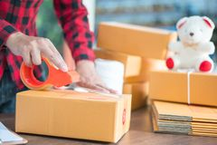Shipping shopping online ,young start up small business owner writing address on cardboard box at workplace.small business royalty free stock photography
