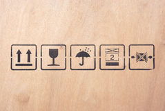 Shipping symbols. Various shipping symbols/icons printed on a wooden crate Stock Image