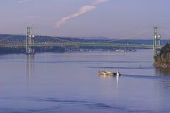Shipping in Tacoma Narrows. Tugboat pushes barge beneath Tacoma Narrows Bridge Royalty Free Stock Photos