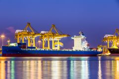Shipping working loading containers. By crane in ship on the night Royalty Free Stock Image